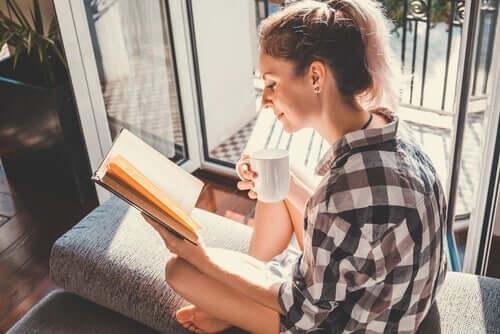 Bir kapının yakınında, güneş altında kitap okuyan bir kadın.