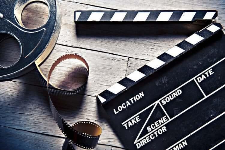 Yerde klaket ve filmleri dışarı taşmış film makarası