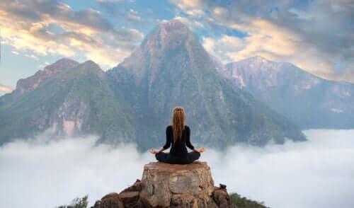 Bir dağın tepesinde meditasyon yapan bir kadın.