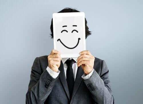 Üzerinde mutlu bir surat olan bir kağıdı yüzünün önünde tutan bir adam.