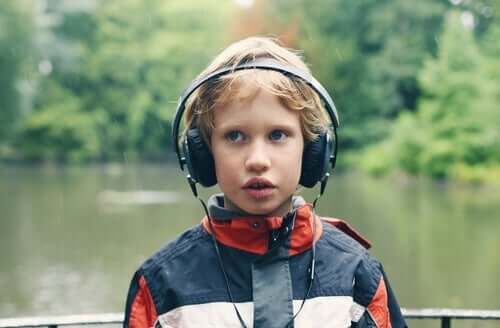 Doğanın içerisindeki bir alanda kulaklıkla müzik dinleyen otizmli çocuk.