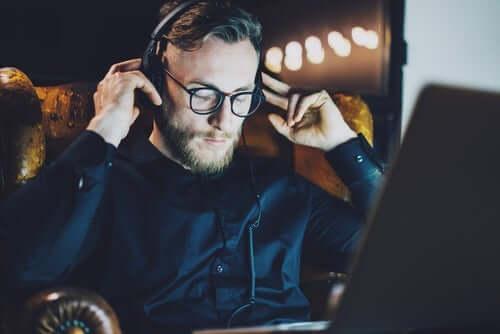 dizüstü bilgisayarında müzik dinleyen adam