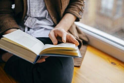 Pencerenin yanında kitap okuyan bir kişi.