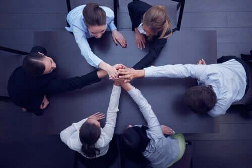 İş birliğini temsil edecek şekilde ellerini bir araya koymuş çalışanlar.