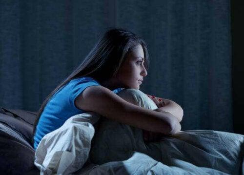 Uyuyamamış, yatağının içerisinde oturan bir kadın.