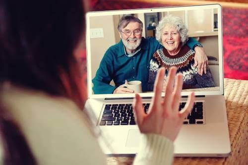 Dede ve ninesi ile videolu konuşma yapan bir kadın.