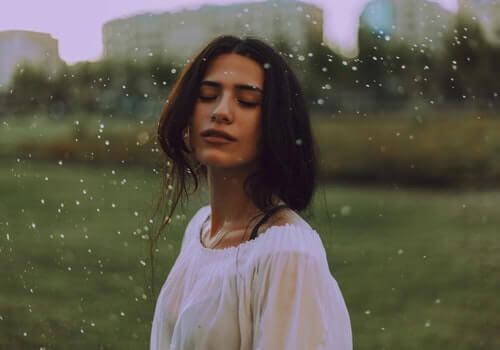 Gözleri kapalı bir şekilde, dışarıda yağmurun altında duran bir kadın.