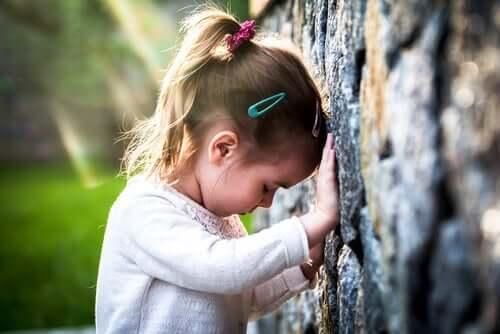 Yüzünü duvara dönmüş bir şekilde yere bakan bir kız çocuğu.