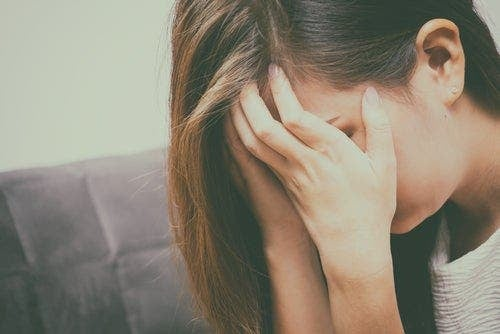 Yüzünü kapatmış bir şekilde ağlayan bir kadın.