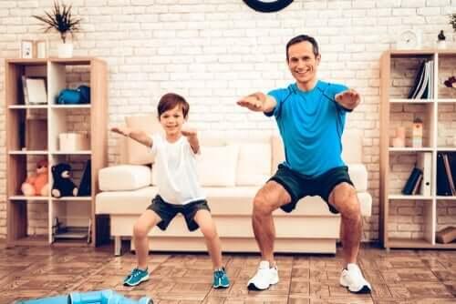 Babası ile birlikte evde egzersiz yapan bir oğlan çocuğu.
