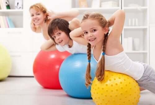 Evde anneleri ile birlikte egzersiz yapan çocuklar.