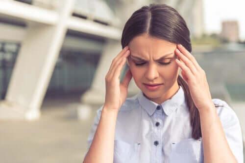 Stresli durumlar dolayısıyla baş ağrısı çeken bir kadın.