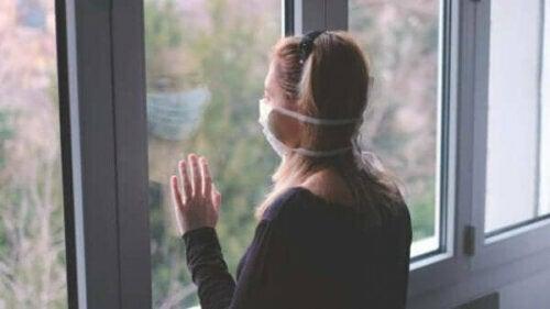 Yüzünde maske ile pencereden bakan bir kadın.