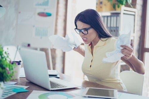 Öfkeli bir şekilde bilgisayarına bakan bir kadın.