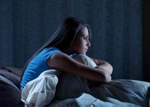 Uykusuzluk hastalığının sonucu gece yatakta oturan kadın