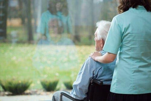 Camdan bakan tekerlekli sandalyedeki bir adam.