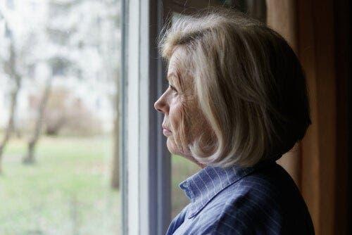 düşünceli bir şekilde camdan bakan yaşlı kadın