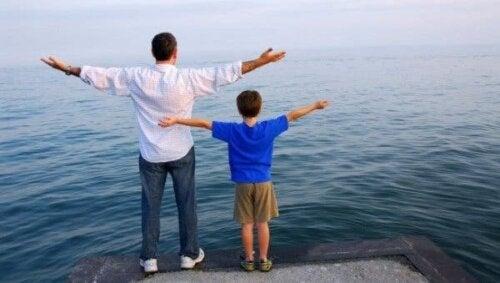 Kollarını açarak denize bakan bir çocuk ve bir yetişkin.