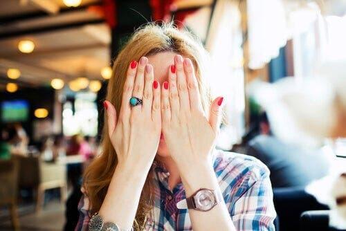 eliyle yüzünü kapatan utangaç kadın