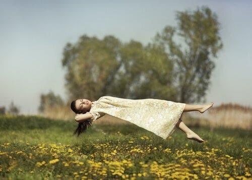 Bir tarlanın üstünde havada süzülen bir kadın.