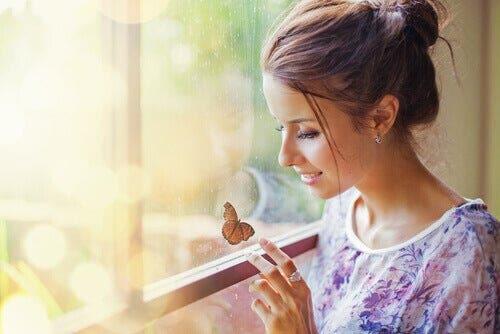 Parmağına konmuş kelebeğe bakan kadın.