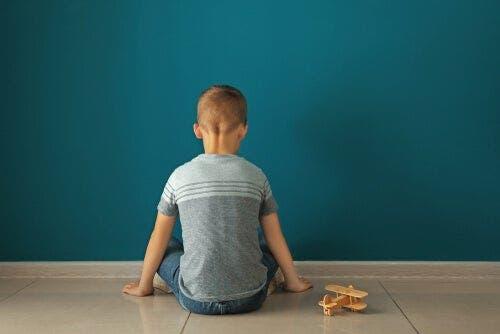 Duvara bakar şekilde yere oturmuş otistik bir çocuk.