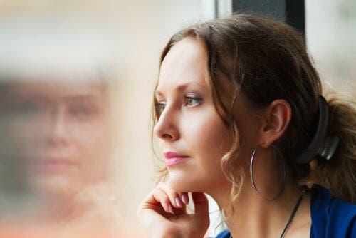 Bir pencerenin yanında oturan bir kadın.