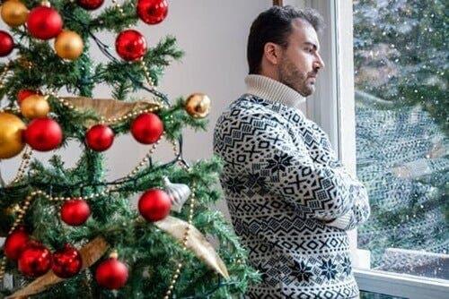 Bir yeni yıl ağacının yanında durmuş pencereden bakan bir kişi.