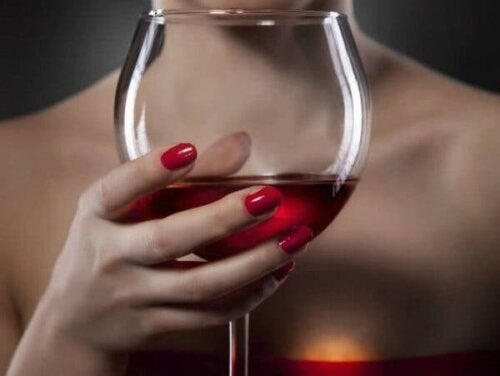 Bir kadının elinde tuttuğu bir şarap kadehi.