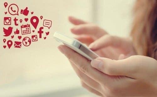 Telefonunu kullanarak sosyal ağlarda dolaşan bir kişi.