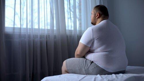 Yatağında oturmuş camdan bakan obez adam
