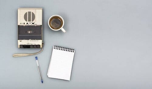Bir kayıt cihazı, bir kupa kahve, bir kalem ve bir defter.