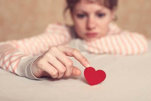 Üzgün bir kadın kalple oynuyor