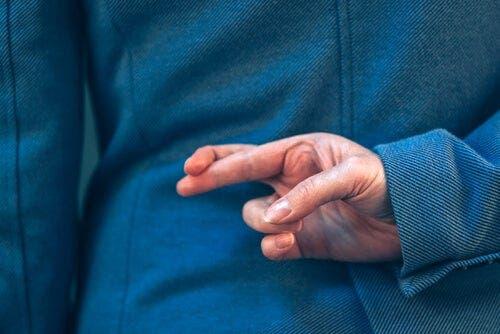 Parmaklarını çaprazlayarak yalan söyleyen bir kişi.