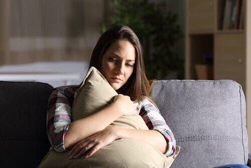 Bir yastığa sarılmış bir kadın.
