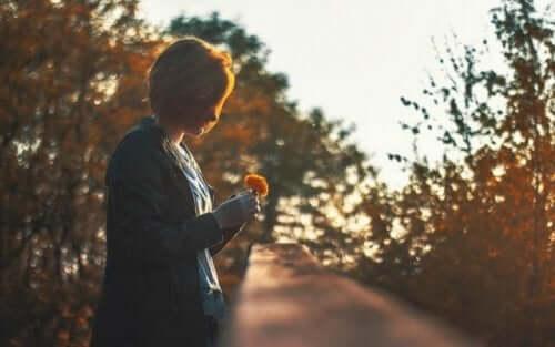 Elinde çiçek tutan bir kadın.