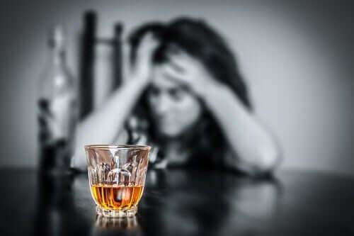 Arka planda bulanık görünen bir kadın ve önündeki net alkol dolu bardak.