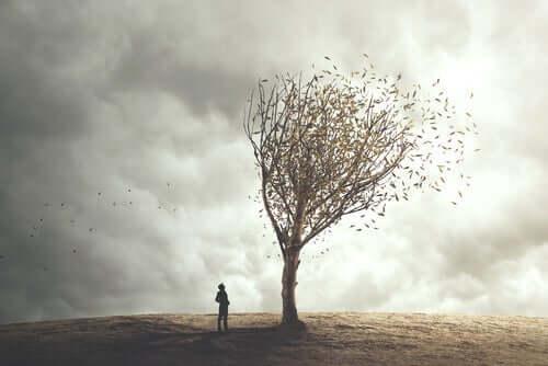 Kuru bir ağacın önünde yalnız duran bir kişi.