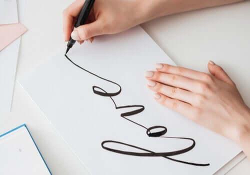 beyaz kağıt üzerine yazı yazan el ve harf yazma hobisi