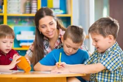 masada çizim yapan üç çocuk ve bir yetişkin kadın