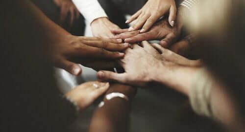 Ellerini bir daire olarak birleştirmiş kişiler.
