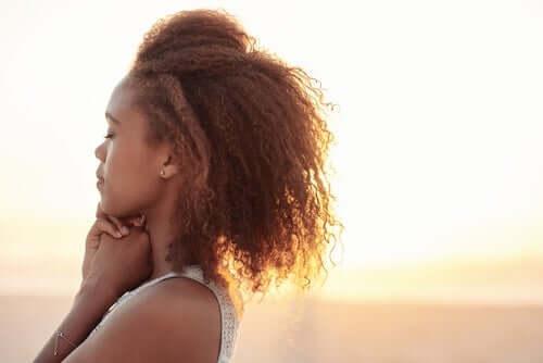güneş ışığında huzurlu bir şekilde duran kıvırcık saçlı kadın