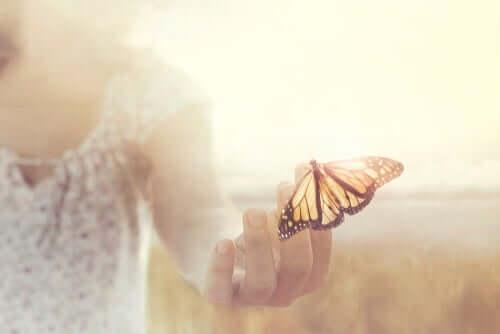 Elinde kelebek tutan bir kadın.