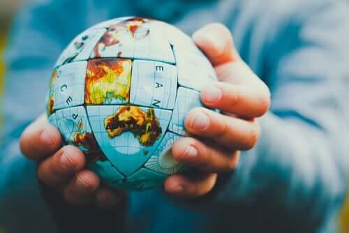 Dünya şeklinde bir puzzle tutan bir kişi.