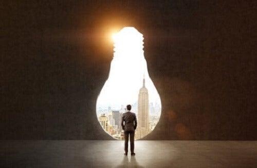 Ampul şeklindeki büyük bir açıklıktan şehre bakan bir adam.