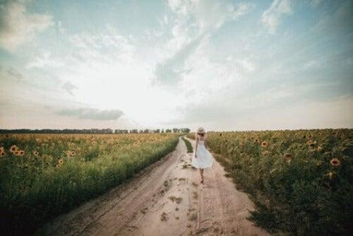 Ayçiçekleri ile dolu bir yolda yürüyen bir kadın.