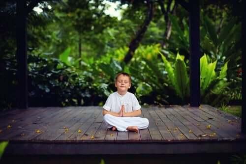 Kendisine bir barış köşesi bulmuş, meditasyon yapan bir çocuk.