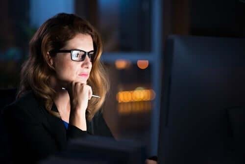 Karanlıkta, bilgisayarında çalışan bir kadın.