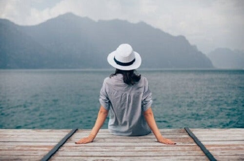 Oturduğu iskeleden denizi izleyen bir kadın.