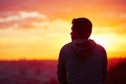 Gün batımına bakarak bir şeyler düşünen bir adam.